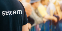 Security officer in front of a crowd of people who are standing behind a barrier