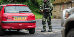 An improvised explosive device disposal specialist searching a car as part of IEDD training