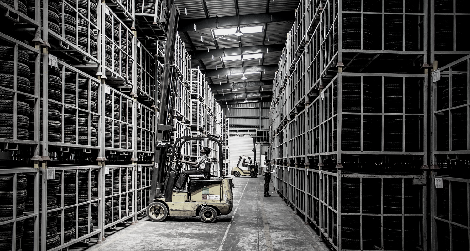 Rows of shelving in a technical warehouse interior with items being moved by a fork-lift truck